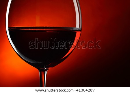 Glass of red wine close-up over deep red background - stock photo