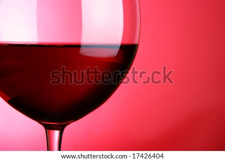 Glass of red wine close-up over red background - stock photo