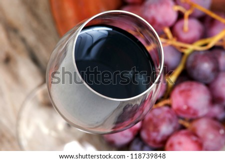 Glass of red wine closeup and purple grapes on rustic wood background.Alcohol,wine making. - stock photo