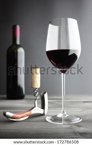 Glass of Red Wine, corkscrew and Bottle, selective focus