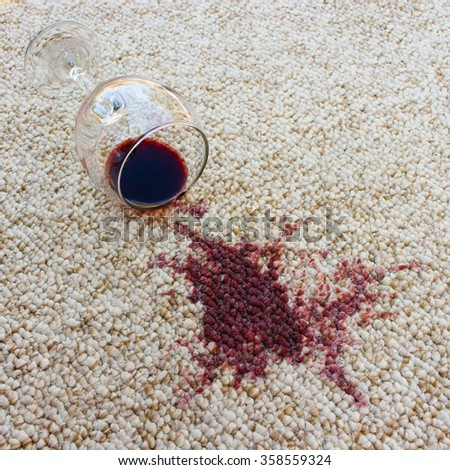 glass of red wine fell on carpet, drink spilled on floor - stock photo