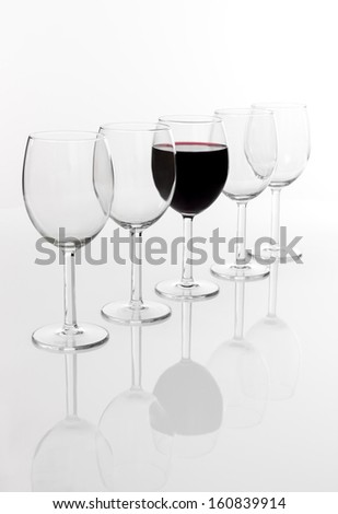 Glass of red wine in a row of empty glasses, with reflection, on white background. - stock photo