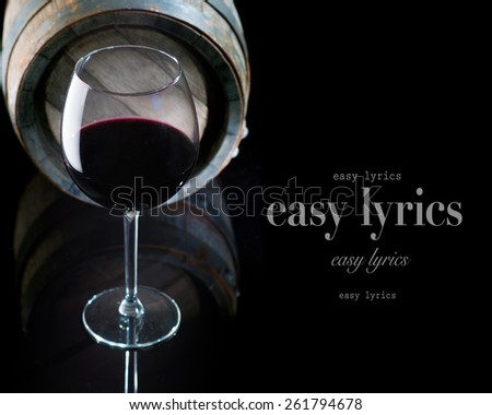 glass of red wine near the barrel