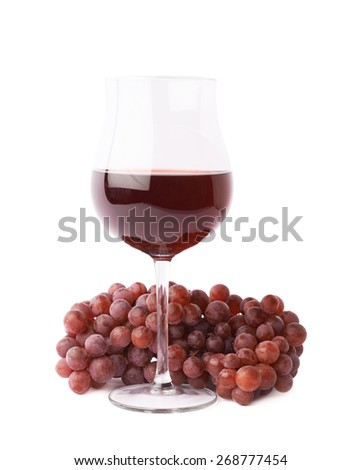 Glass of red wine next to a branch of grapes isolated over the white background - stock photo