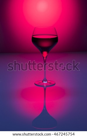 Glass of red wine on a purple background / Red wine / Nadale