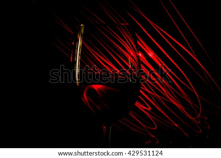 Glass of red wine on a red background abstract light stripes on a black background - stock photo