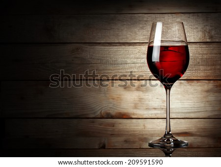 Glass of red wine on a young wooden background - stock photo