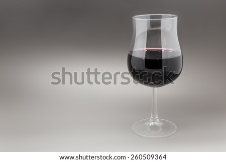 Glass of red wine on grey gradient background