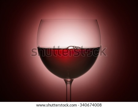 glass of red wine on red background - stock photo