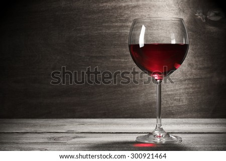 Glass of red wine on rustic wooden background with copy space. - stock photo