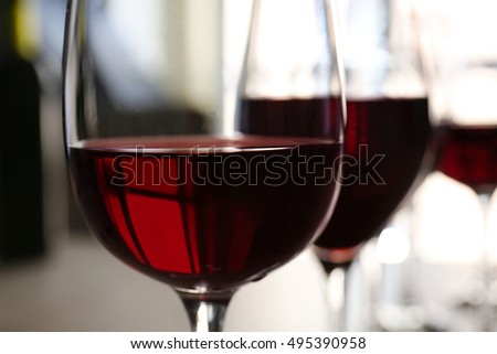 Glass of red wine on table in restaurant, closeup