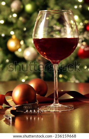 Glass of red wine on table with holiday tree in background - stock photo