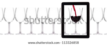 glass of red wine on tablet computer screen isolated on a white background - stock photo