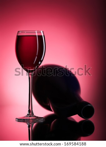 glass of red wine on the fallen pitcher burgundy background