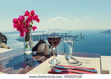 Glass of red wine on the table overlooking the volcano of Santorini