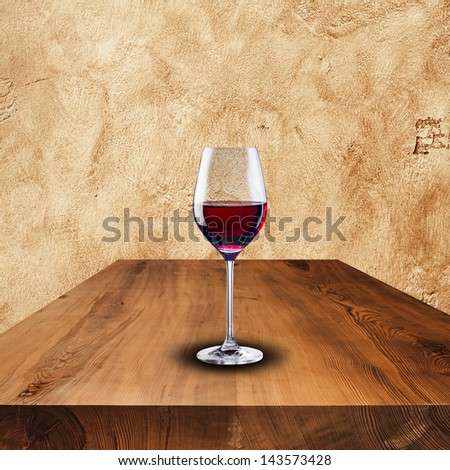 Glass of red wine on wood table and grunge wall