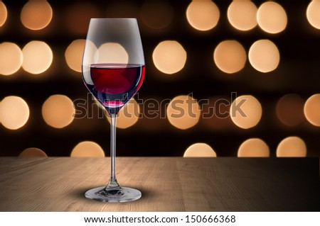 Glass of red wine on wood table and night scene