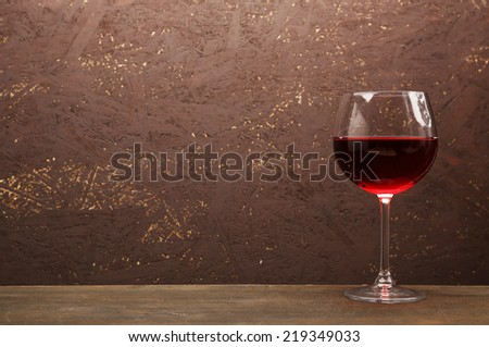 Glass of red wine on wooden table on wooden wall background