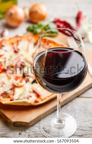 Glass of red wine, pizza on background - stock photo