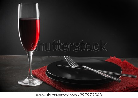 Glass of red wine, plates, silverware and napkin on dark wooden table.