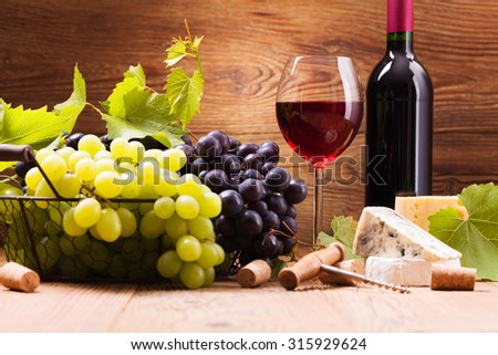 Glass of red wine, served with grapes and cheese on a wooden background