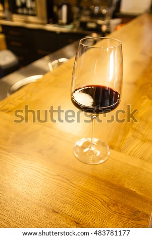 Glass of red wine standing on a bar  counter in a fancy wine restaurant