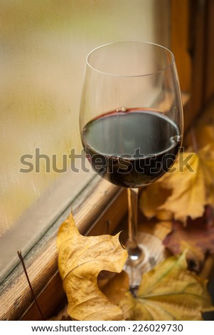 Glass of red wine standing on windowsill with autumn leaves and a fogged window in the background