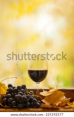 Glass of red wine standing on windowsill with autumn leaves and grapes with a fogged window in the background