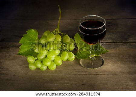 glass of red wine with a cluster of grapes on old wooden table - stock photo