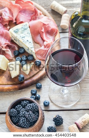 Glass of red wine with antipasto - stock photo