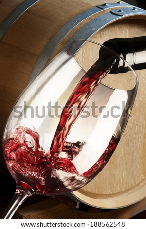 glass of red wine with barrel
