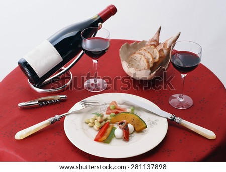 Glass of red wine with bottle  - stock photo