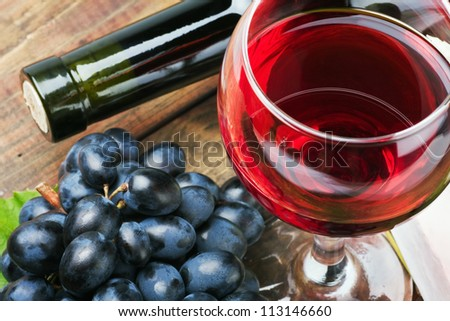 glass of red wine with bottle and grape - stock photo