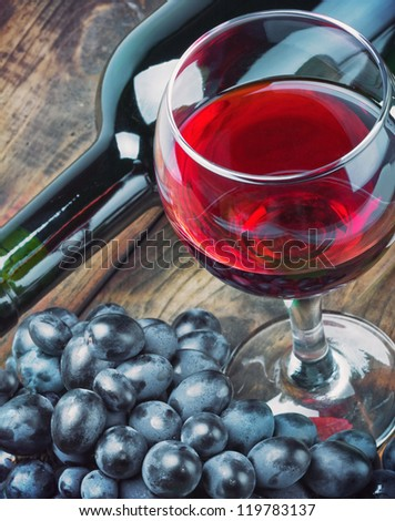 glass of red wine with bottle and grape