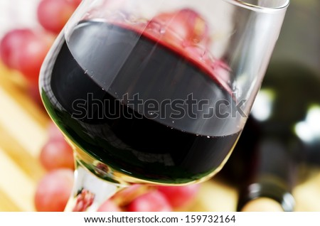 Glass of red wine with bottle and grapes in the background. - stock photo