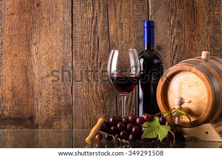 Glass of red wine with bottle barrel grapes and wooden background - stock photo