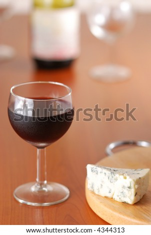 Glass of red wine with bottle & cheese
