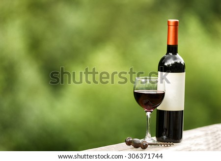 Glass of red wine with full bottle and corkscrew on rustic wood outdoors. Selective focus on front of wine glass with shallow depth of field on horizontal layout.  - stock photo