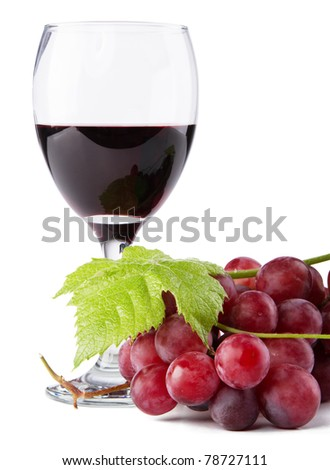 Glass of red wine with grapes on foreground