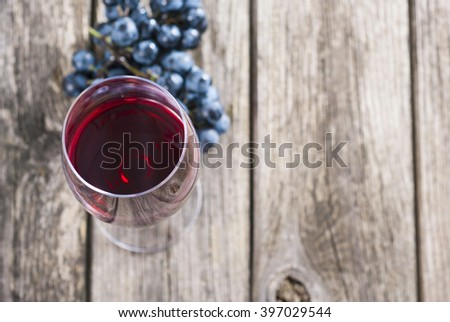 glass of red wine with grapes on rusty wooden table