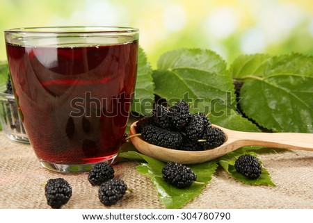 Glass of refreshing mulberry juice with berries on bright background - stock photo