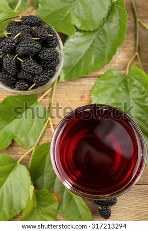 Glass of refreshing mulberry juice with berries on table close up - stock photo