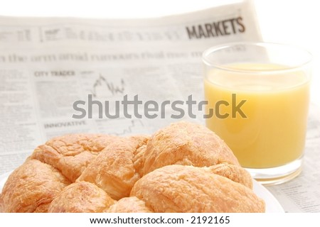 Glass of refreshing orange fruit juice and croissant over business paper with graphs and word 'market', macro - stock photo