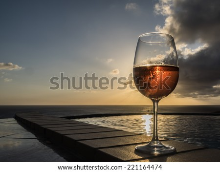 Glass of rose wine in the sunset Curacao a Caribbean island in the Dutch Antilles - stock photo
