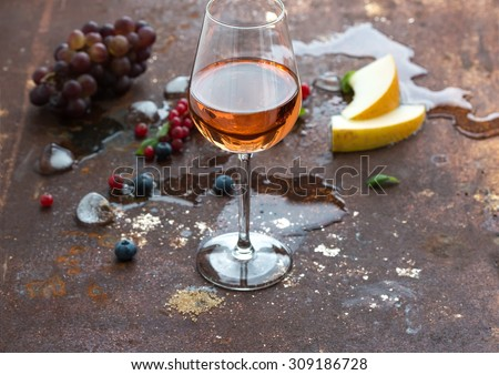 Glass of rose wine with berries, melon, grapes and ice on grunge rusty metal background, copy space - stock photo