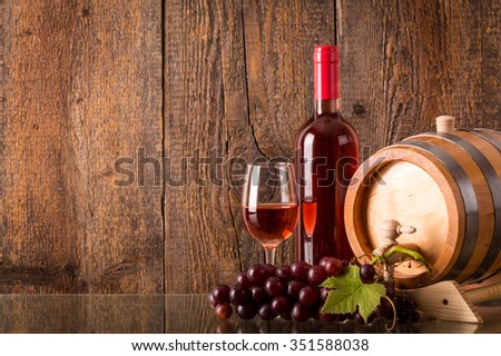 Glass of rose wine with bottle barrel grapes and wooden background - stock photo