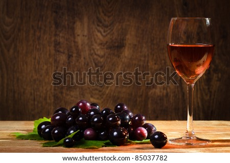 Glass of rose wine with dark grapes - stock photo