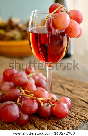 glass of rose wine with grapes on wooden table - stock photo