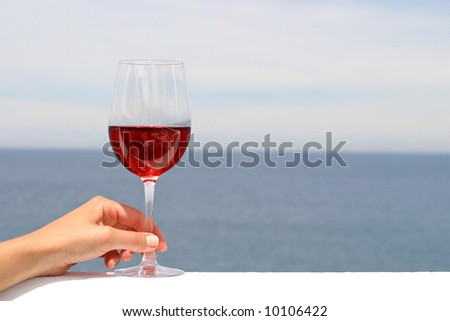 glass of rose wine with the ocean in the background - stock photo
