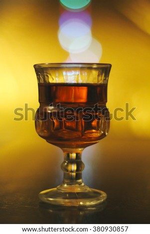Glass of rum with soft yellow light and bokeh